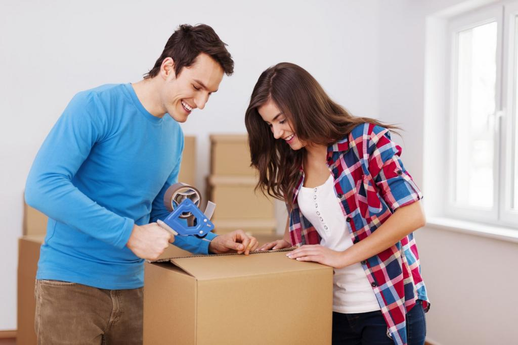 couple packing clothes in box
